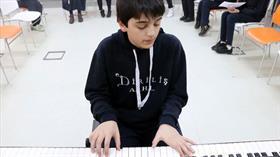Piyanonun tuşlarına kendi besteleri için basıyor